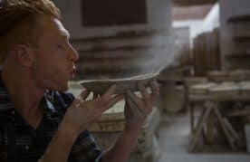 A Picture Of A Man Blowing Pottery Dust Off Of A Bowl