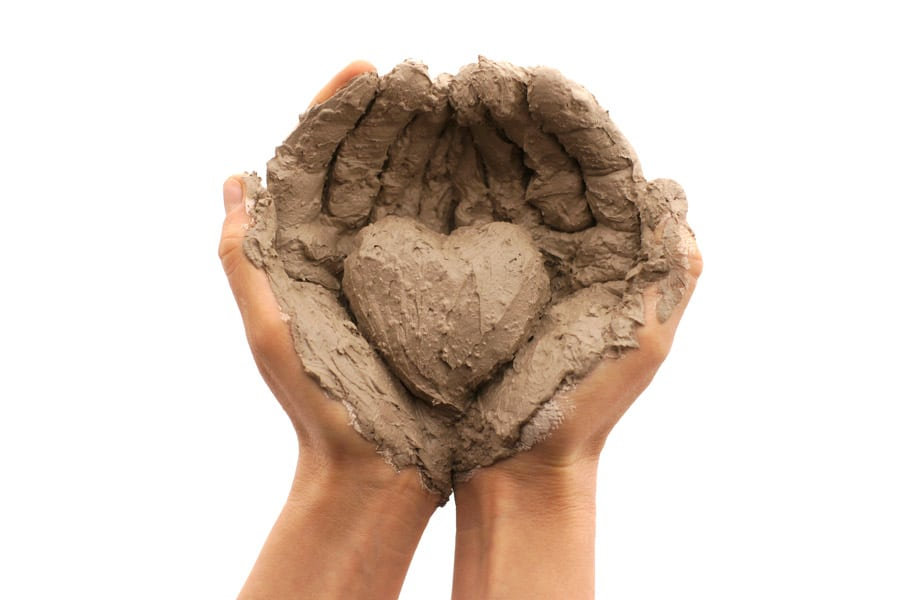 A Picture Of Wet Heart Shaped Pottery Clay Cradled In Open Hands