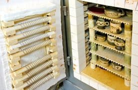 A Picture Of Open Kiln With Pottery Stacked On Kiln Shelves