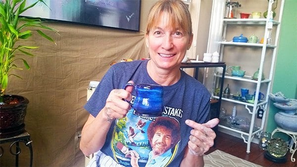 a picture of a potter pointing at a blue mug