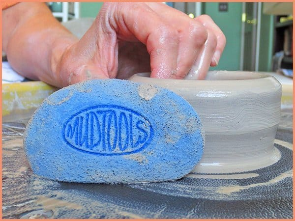 a picture of a potter displaying a blue sponge tool