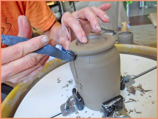 a picture of a potter using a double ended timming tool