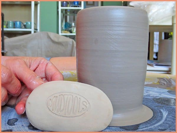 a picture of a potter displaying a white finishing sponge tool