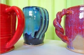 a picture of three finished mugs with clay extruder handles