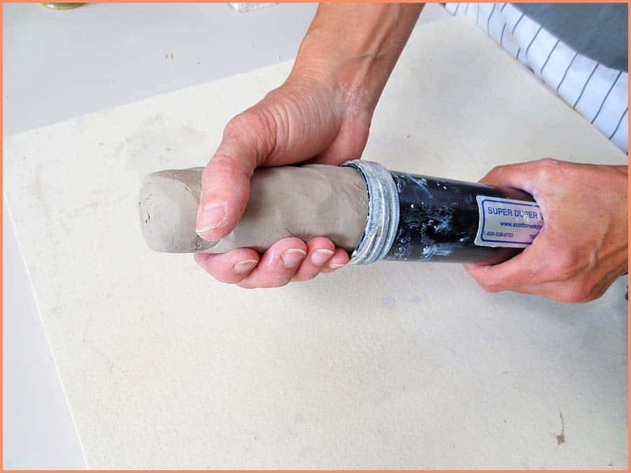 a picture of a potter sliding clay in extruder tube
