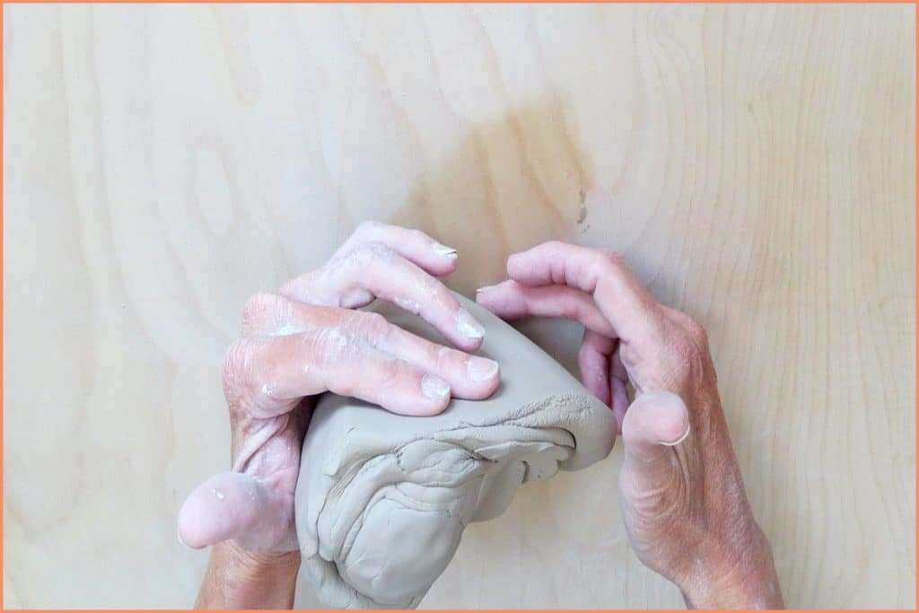 a picture of a potter lifting the spiral wedge up to the left
