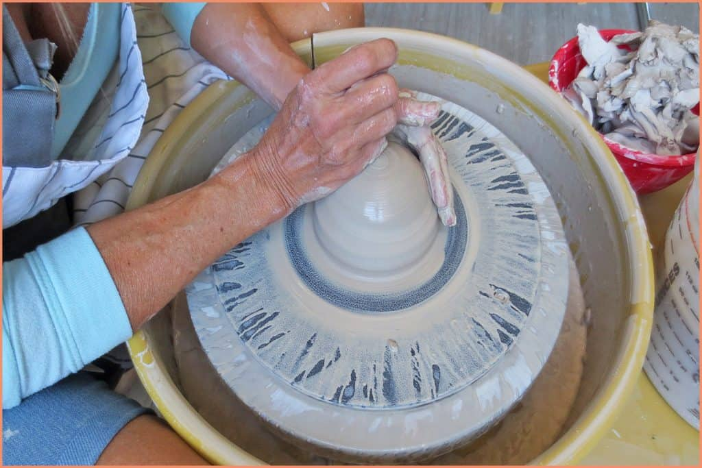 a picture of a potter on the wheel with the clay in a beehive shape