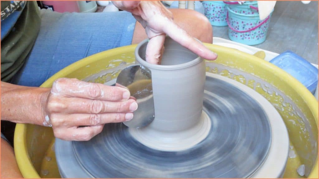 a picture of a potter using a metal scraper on the pottery wheel