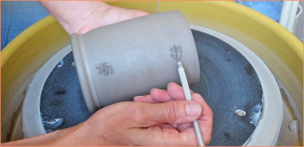 a picture of a potter using a metal wire brush tool