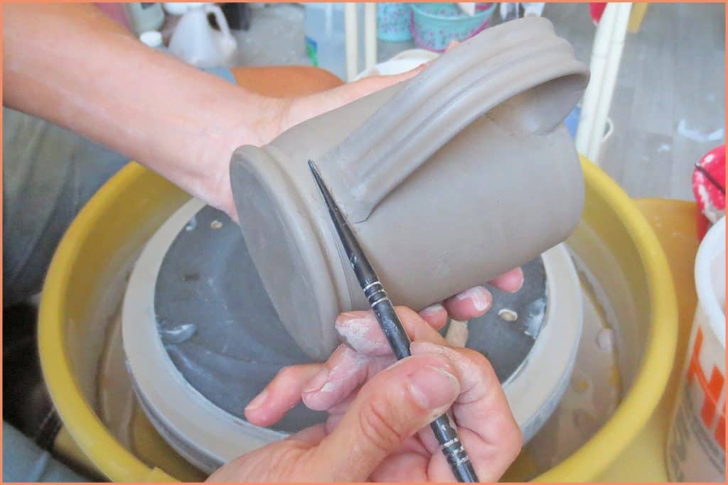 a picture of a potter using a plastic modeling tool