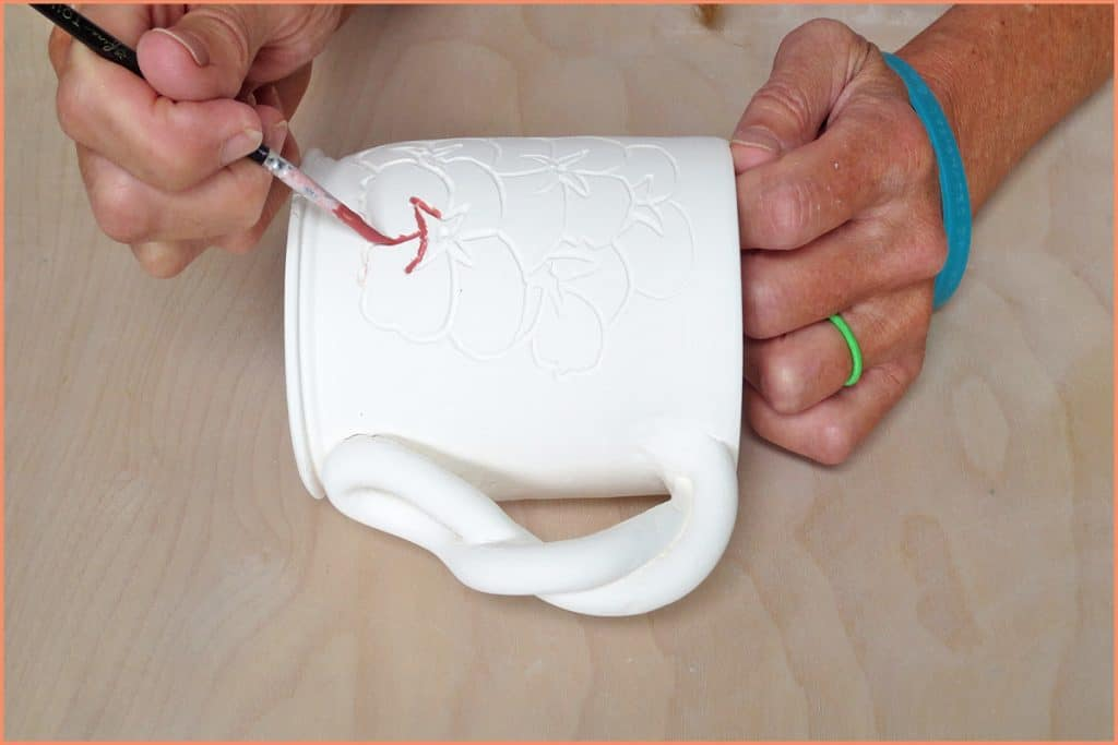 a picture of a potter underglazing with a detail brush