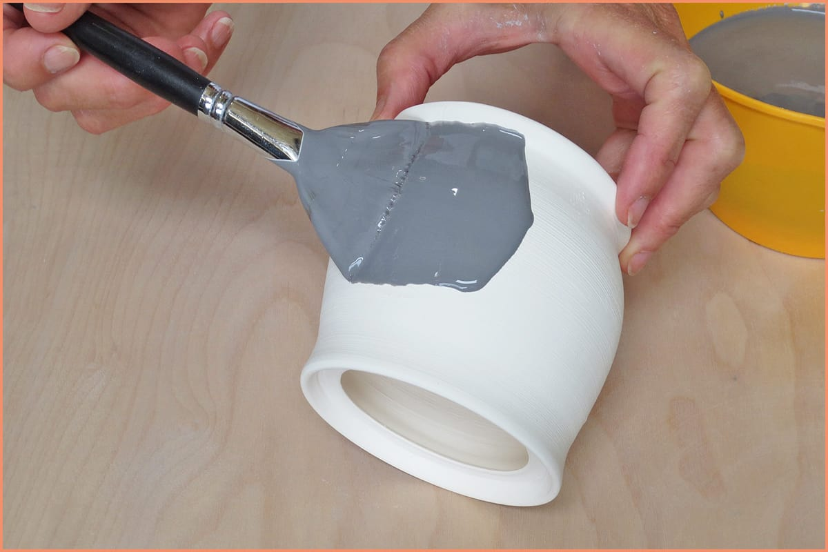 a picture of a potter applying glaze with a fan brush