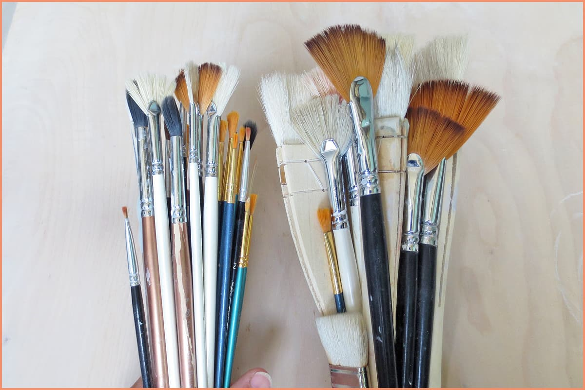 a picture of a potter holding glaze brushes