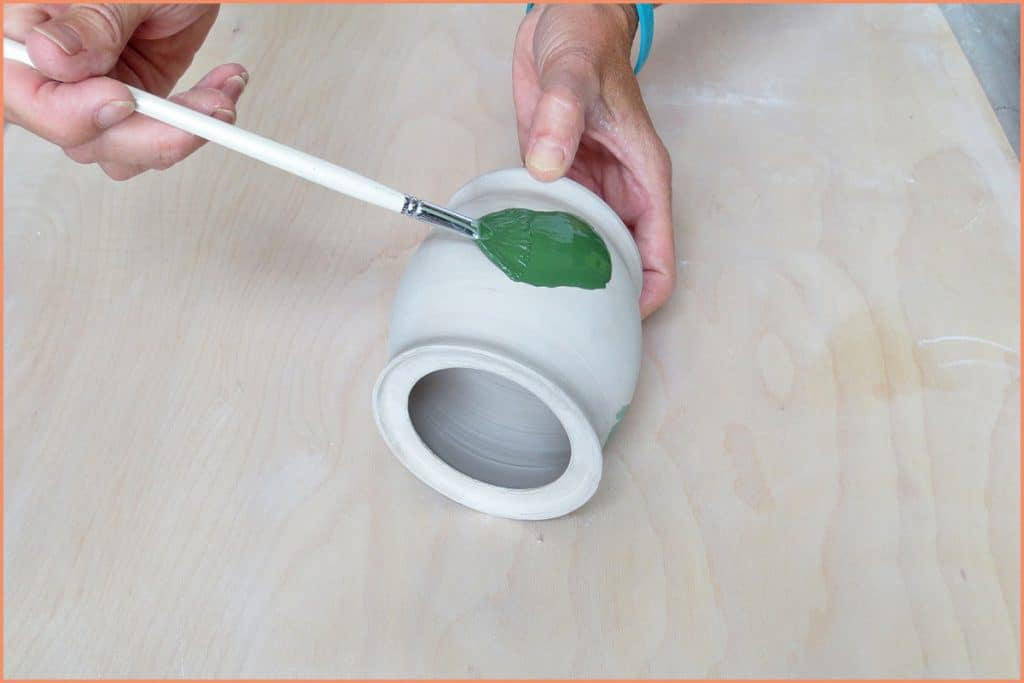 a picture of a potter brushing on underglaze with a firm fan brush