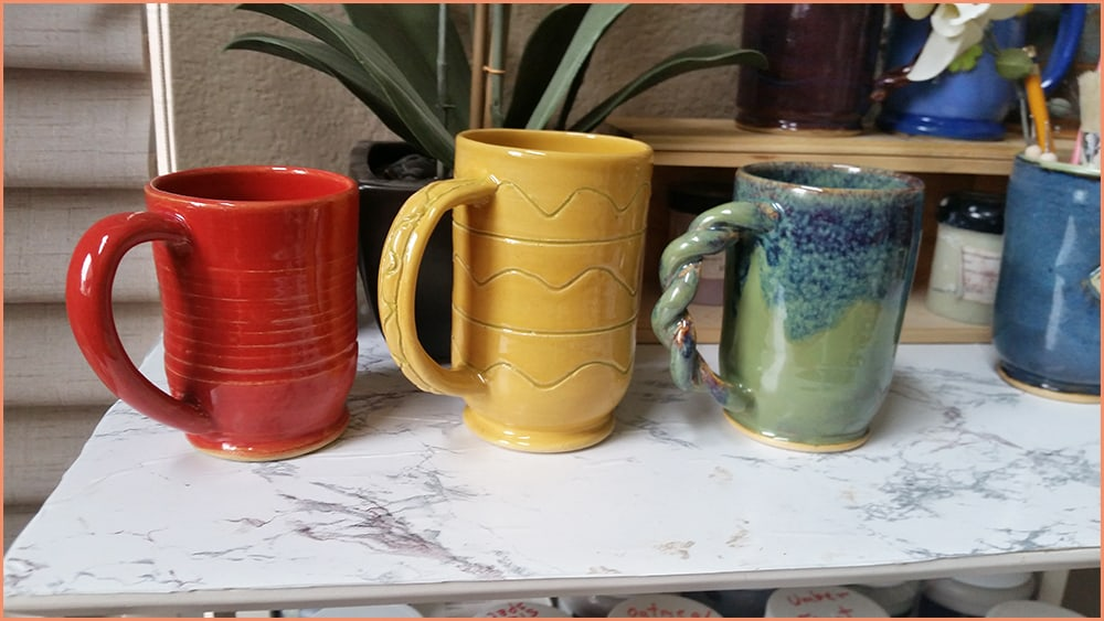 a picture of three brush glazed mugs