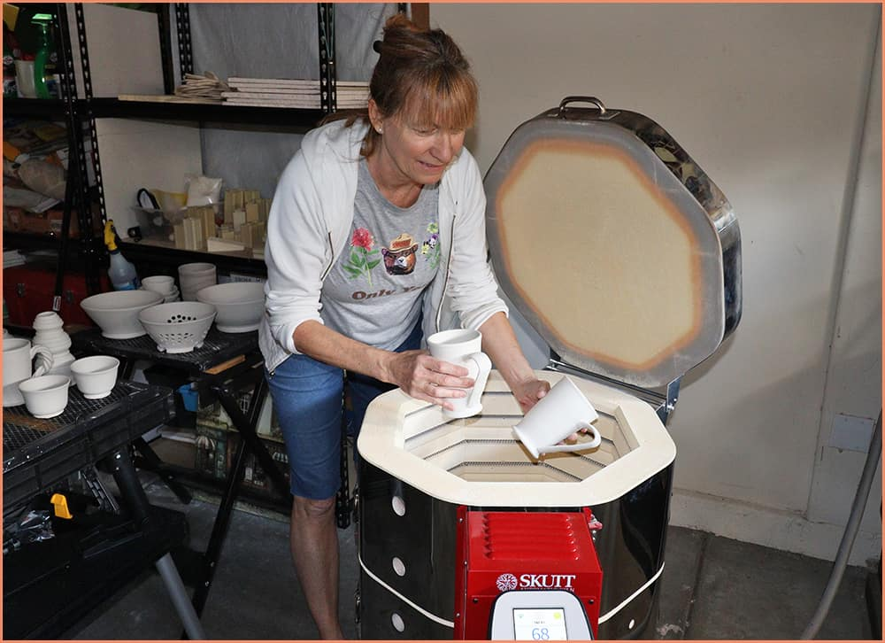 a picture of a potter loading the kiln