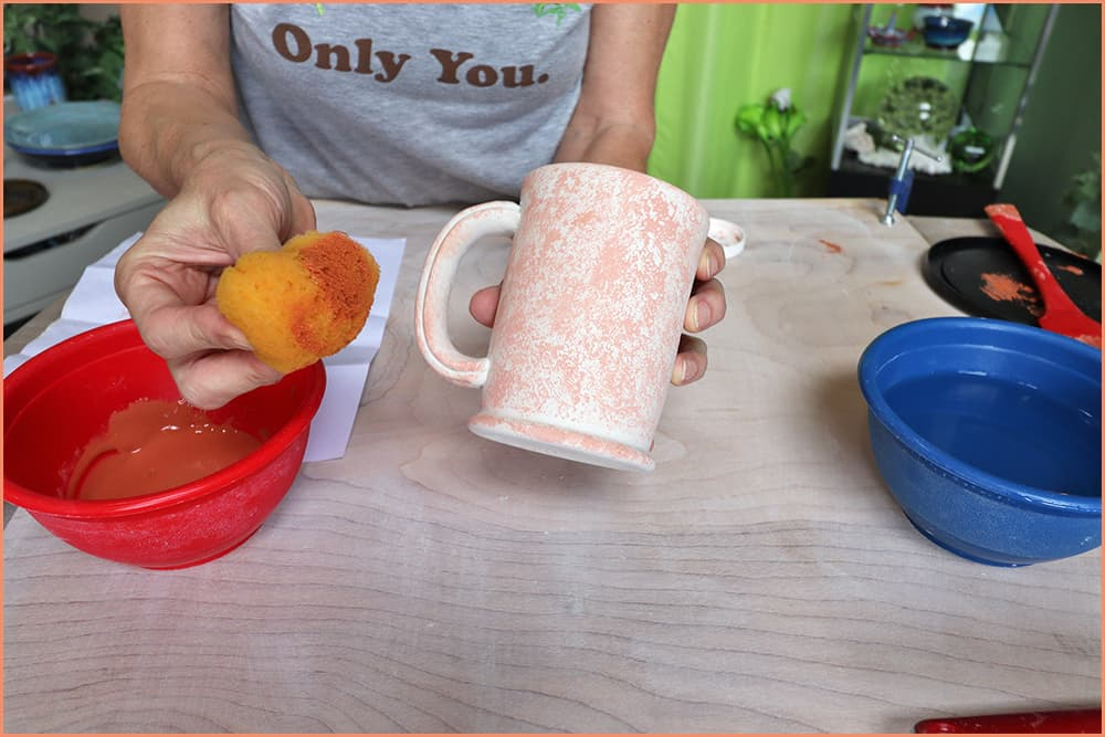 a picture of a holding a sponge underglazed mug