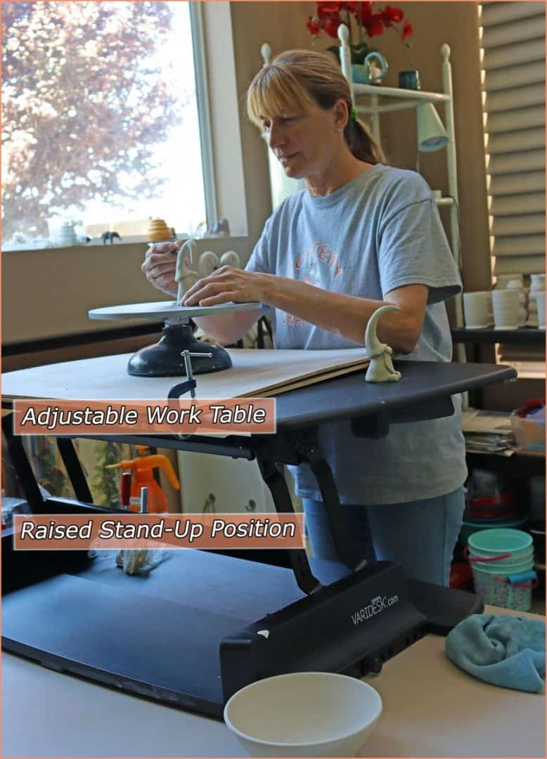 a picture of a potter at adjustable work table raised stand up position