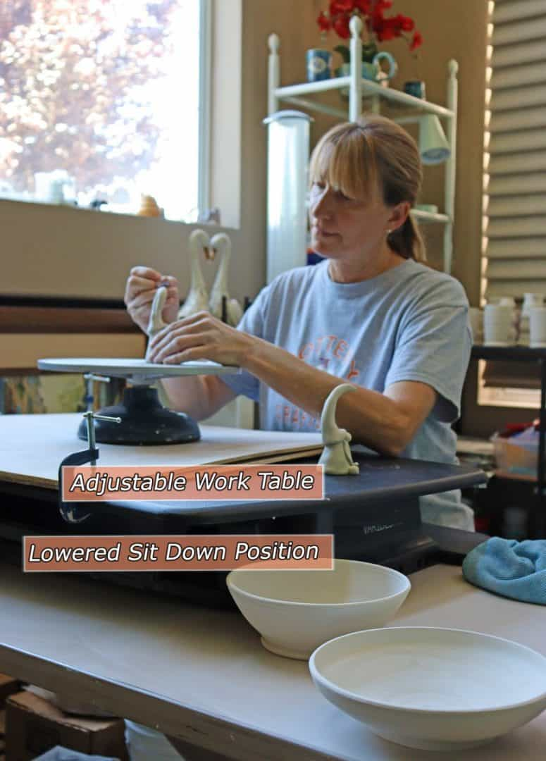 a picture of a potter at adustable work table lowered sit down position