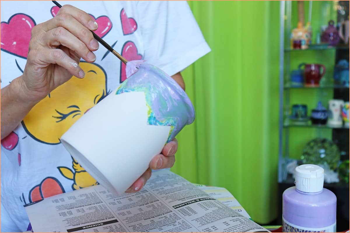 a picture of a potter applying wax resist to a mug
