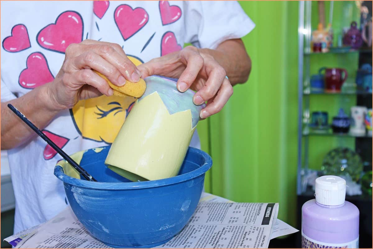 a picture of a potter sponging glaze off the wax resist