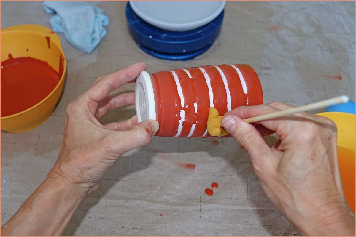 a picture of a potter wiping off glaze wax resist area