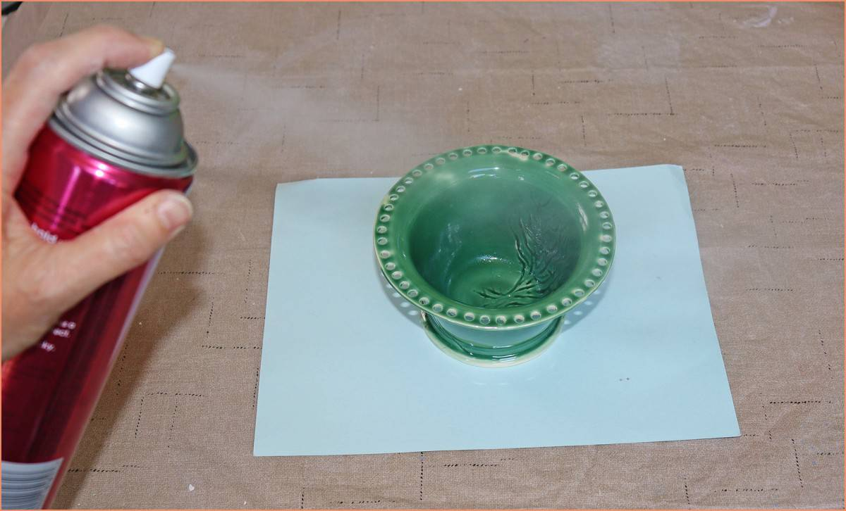 a potter spraying the inside of an earing holder