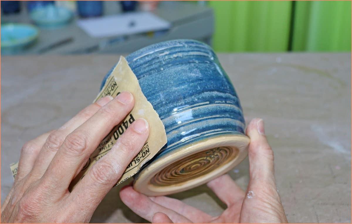 a picture of a potter sanding glazed pottery