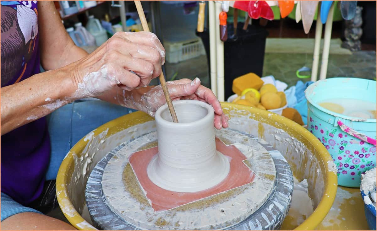a picture of a potter using a sponge on a stick