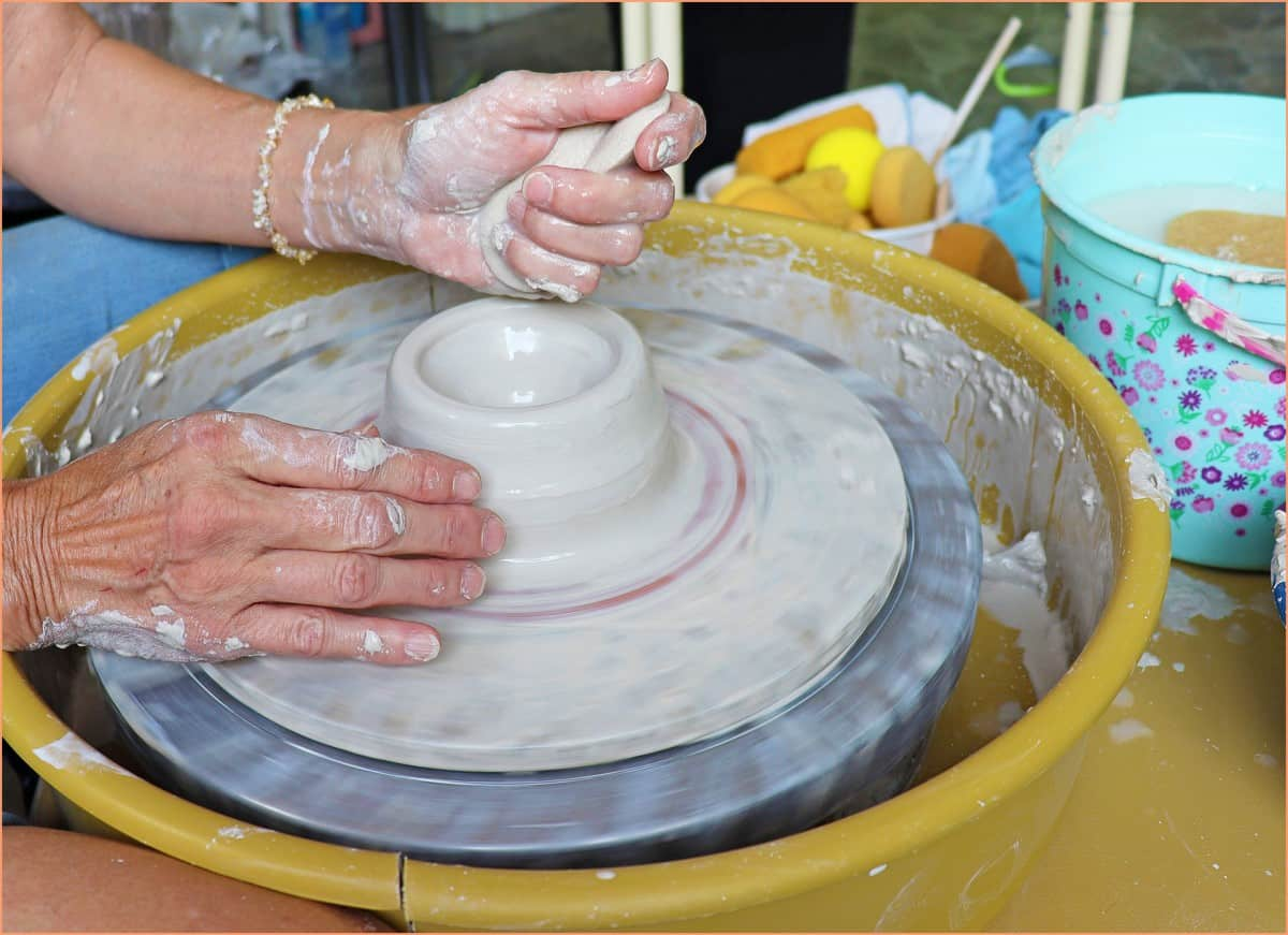 a picture of a potter applying water to clay