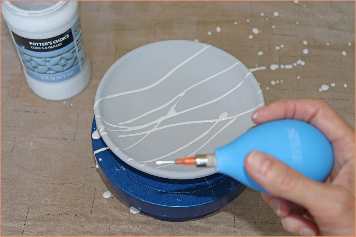 a picture of a potter trail glazing a plate