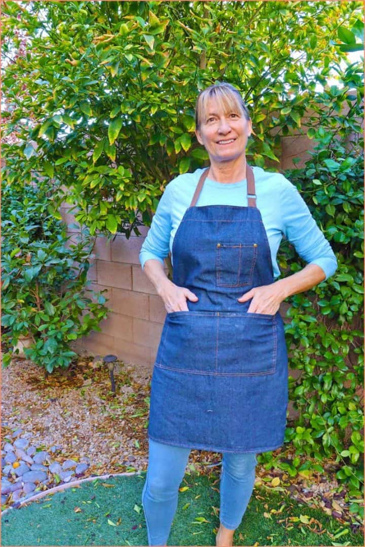 a female standing up and modeling a meychin  blue adjustable denim apron