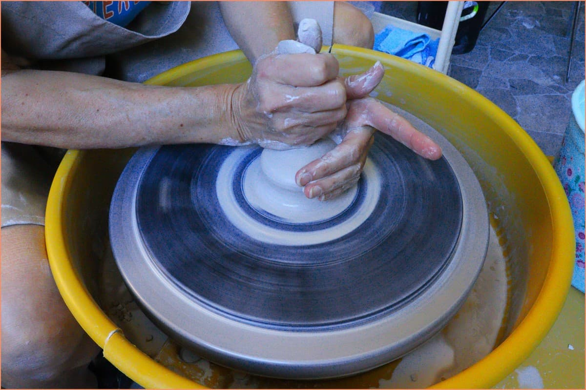 a picture of a potter centing clay