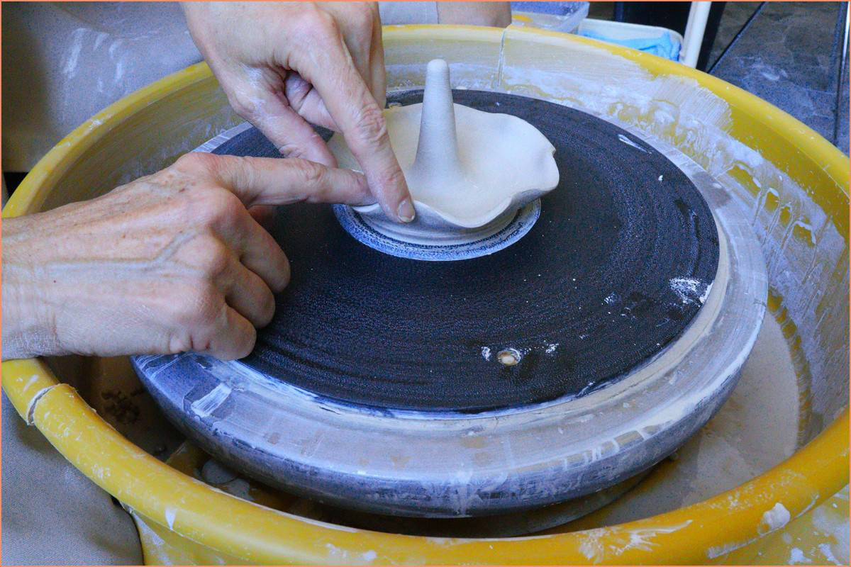 a picture of a potter making a wavy rim