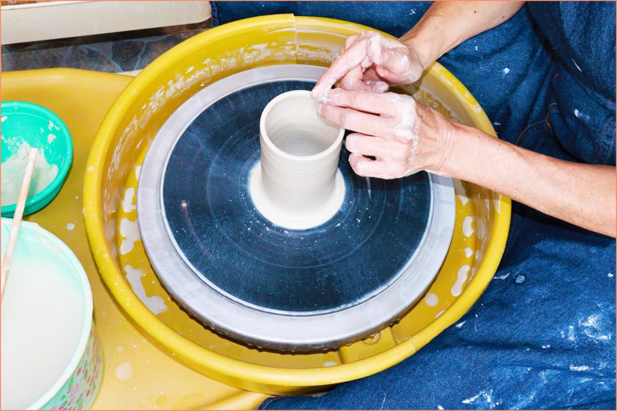 a picture of potter throwing on the wheel