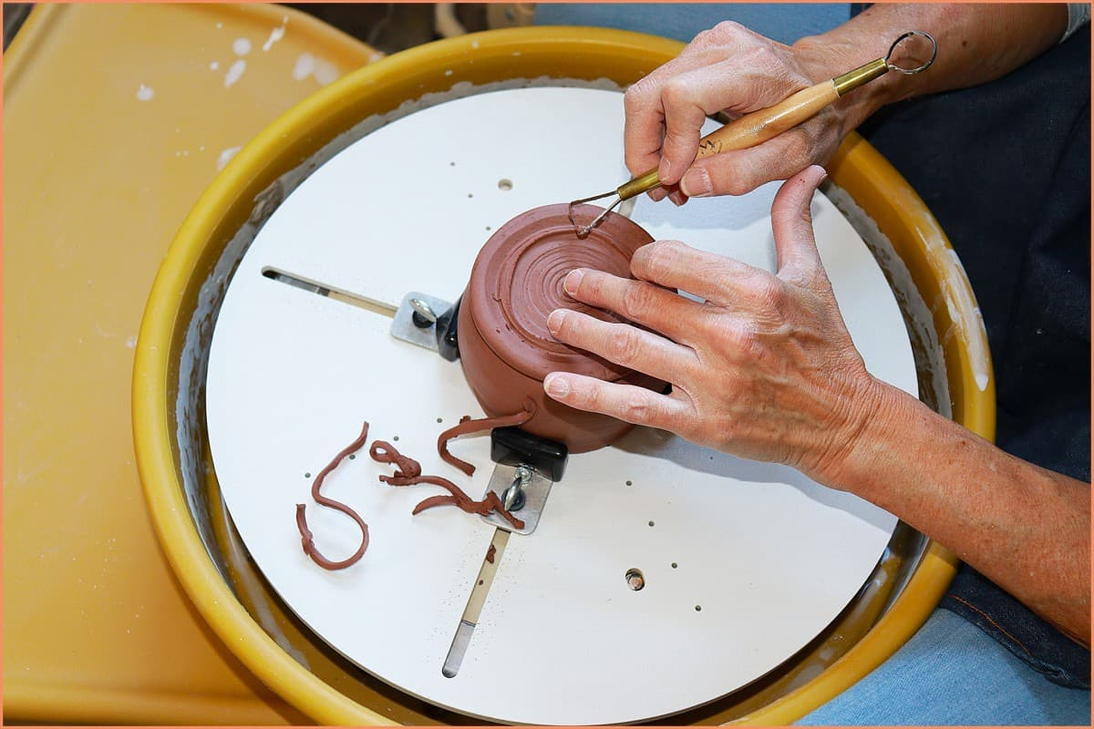 picture of potter trimming pottery