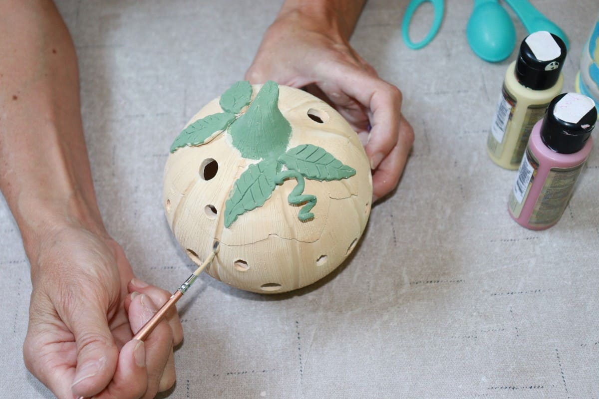 a picture of a potter picture of potter applying underglaze to pumpkin